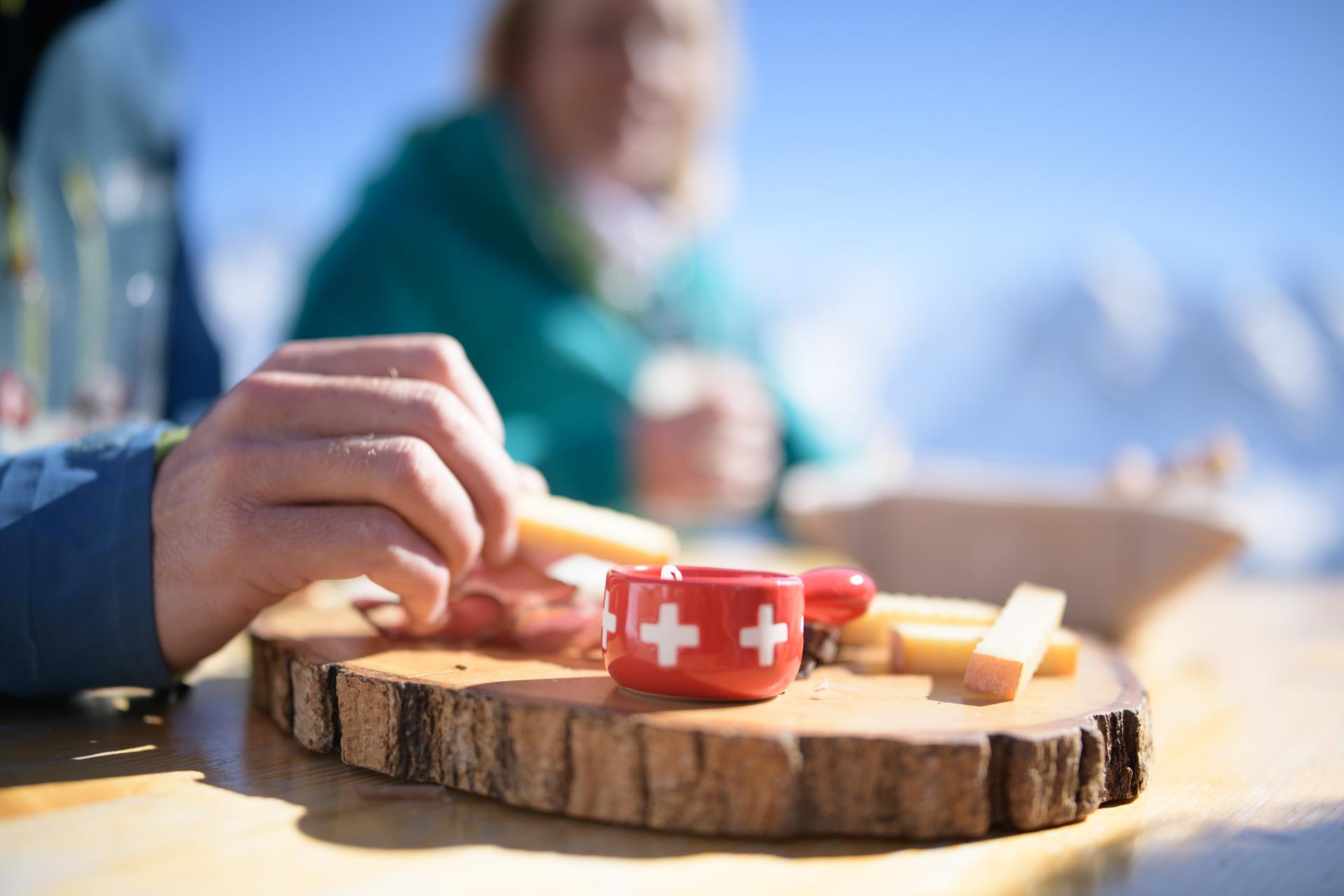 Der Walliser Teller : Ein mit lokalem Käse und Charcuterie garniertes Holzbrettchen.